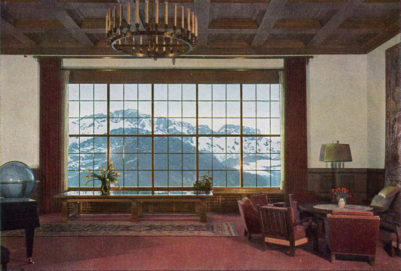 A large window in the great hall looks out onto snowy mountains.